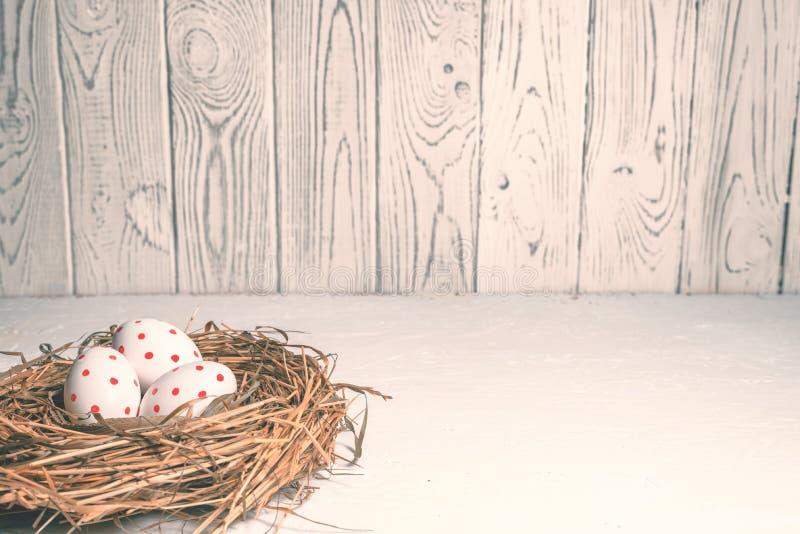 Tres huevos con los puntos rojos en un día de fiesta de Pascua de la jerarquía del heno imagen de archivo libre de regalías