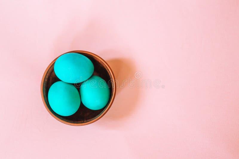 Tres huevos de Pascua de color de la turquesa en una placa de madera en un fondo rosado suave ilustración del vector