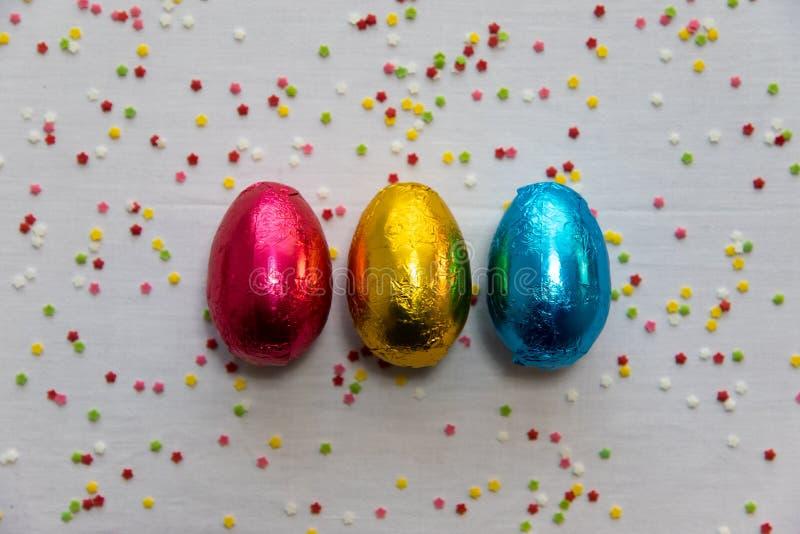 Tres huevos de Pascua coloreados del chocolate en el fondo blanco y el confeti colorido foto de archivo