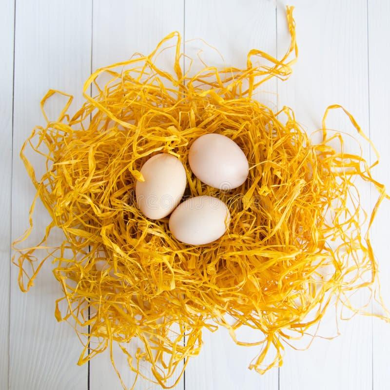 Tres huevos del pollo en la jerarquía decorativa en el fondo de madera blanco foto de archivo libre de regalías