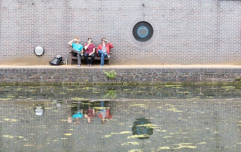 Tres individuos que charlan cerca del canal imagen de archivo