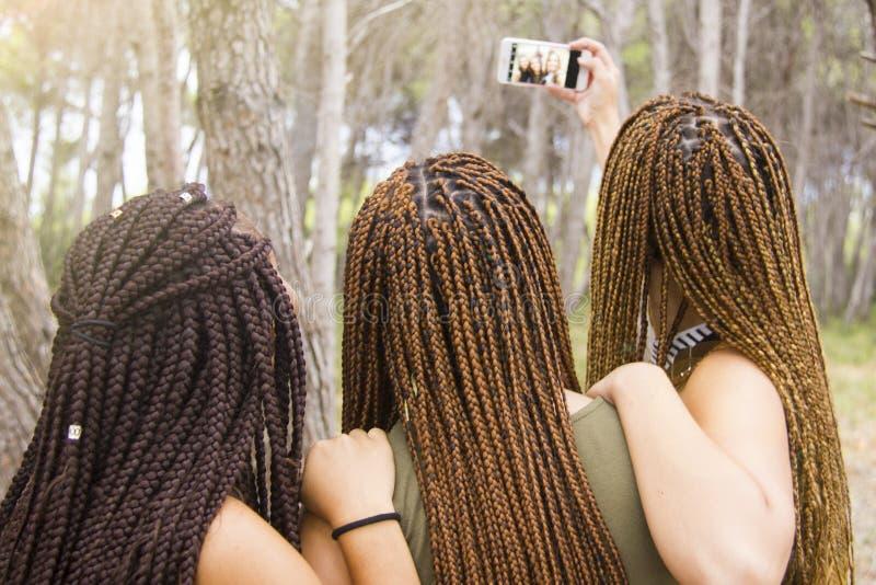 Tres jovenes y muchachas hermosas, con el pelo trenzado, tomando el selfie imágenes de archivo libres de regalías