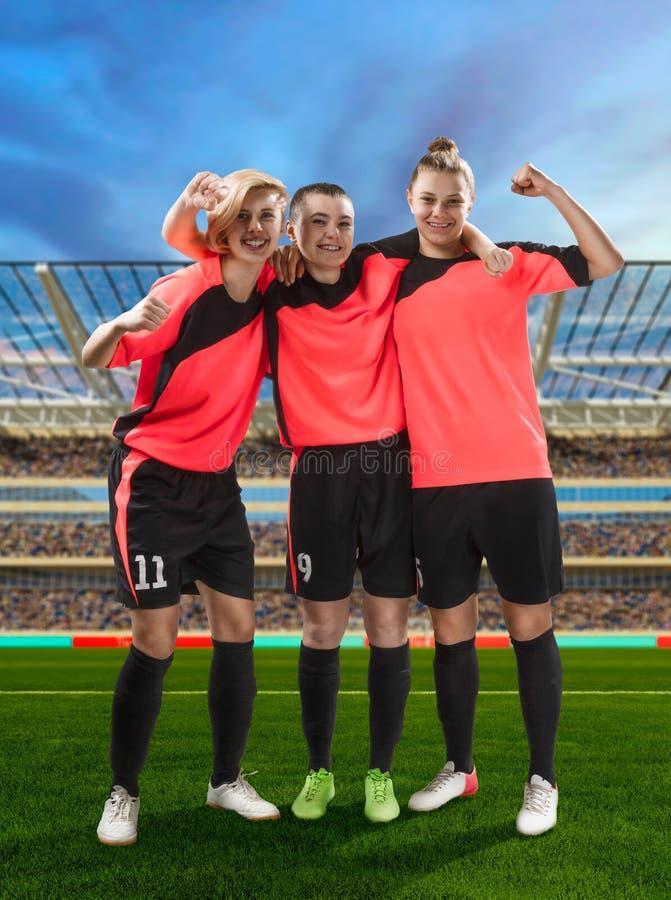 Tres jugadores de fútbol de sexo femenino que celebran la victoria en el fútbol archivado imagen de archivo