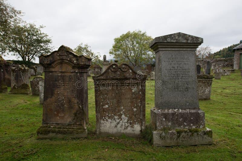 Tres lápidas mortuarias en un cementerio en Escocia fotos de archivo