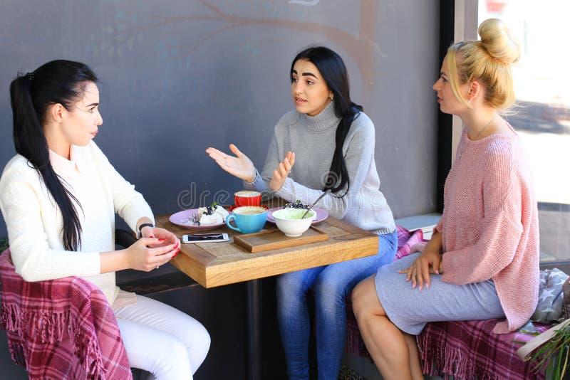 Tres la sonrisa femenina hermosa en café, charla, dice secretos, come, d fotografía de archivo libre de regalías