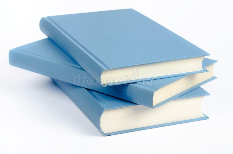 Tres libros azules en un fondo blanco fotografía de archivo