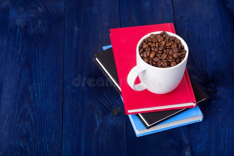 Tres libros y tazas por completo de granos de café foto de archivo libre de regalías