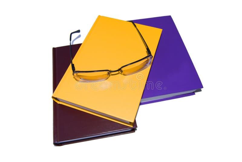 Tres libros y vidrios coloreados en un blanco. foto de archivo