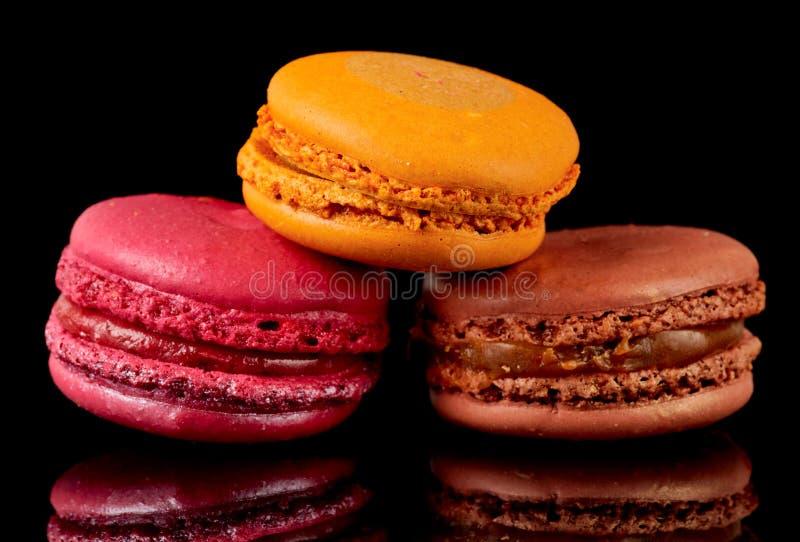 Tres macarons coloridos en fondo negro fotografía de archivo libre de regalías
