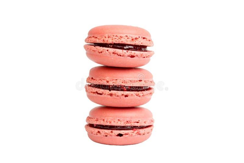 Tres macarrones rosados de la fresa apilan encima de uno a aislaron en el fondo blanco, ninguna sombra fotografía de archivo