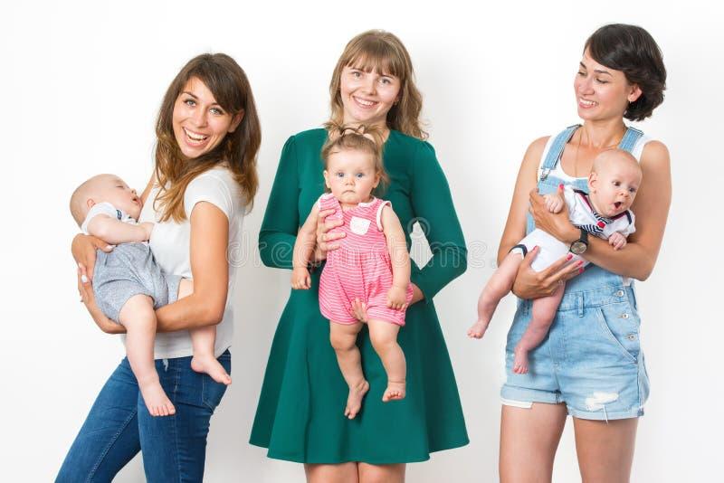 Tres mamáes felices con sus niños jovenes imagen de archivo libre de regalías