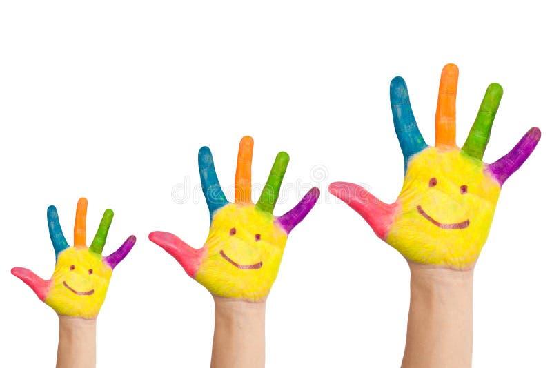 Tres manos coloridas con la sonrisa de la familia fotos de archivo libres de regalías