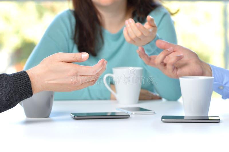 Tres manos de los amigos que hablan en una barra con el teléfono en la tabla foto de archivo
