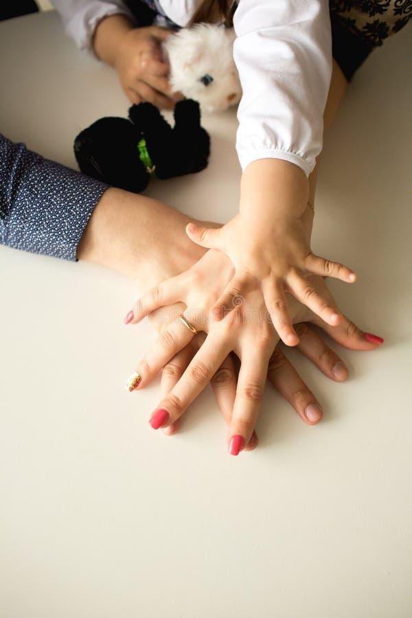 Tres manos en la tabla - bebé, madre y padre foto de archivo