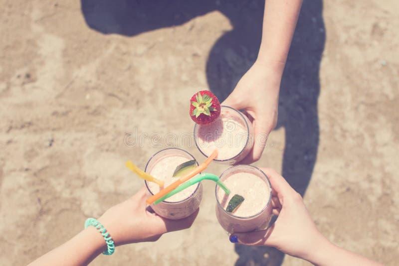 Tres manos femeninas están sosteniendo los batidos de leche de la fresa en el fondo del mar foto de archivo