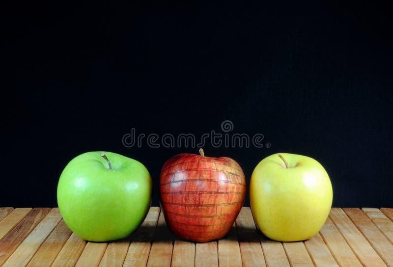 Tres manzanas con la manzana en la textura de la pared de ladrillo En estera de la teca y fondo negro Copie el espacio foto de archivo