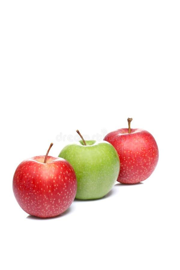 Tres manzanas, dos rojos y un verde aislados en el fondo blanco imagen de archivo libre de regalías