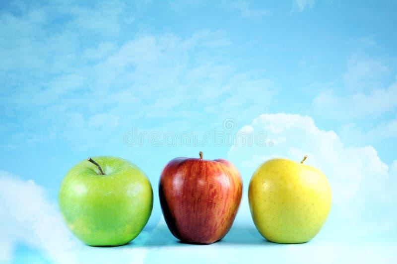 Tres manzanas en el cielo y las nubes brillantes foto de archivo