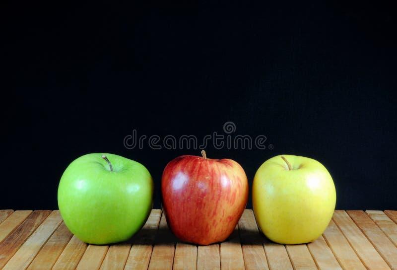 Tres manzanas en estante del teakwood y fondo negro foto de archivo libre de regalías