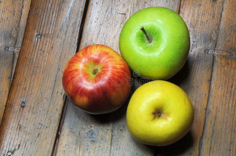 Tres manzanas en fondo de madera foto de archivo