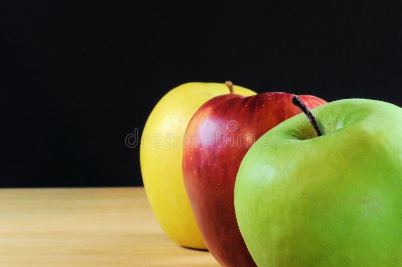 Tres manzanas en fondo negro Foco selectivo imagen de archivo libre de regalías
