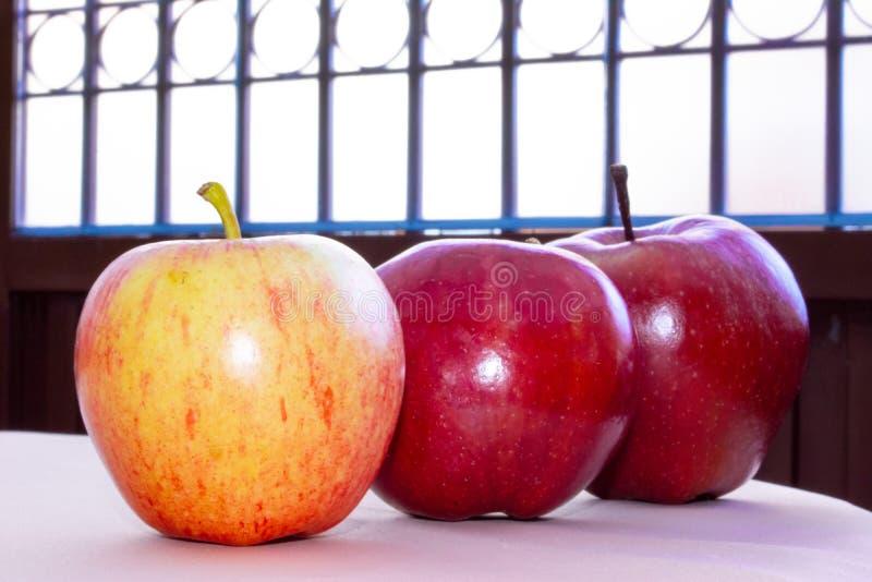 Tres manzanas en línea en la tabla foto de archivo