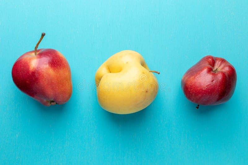 Tres manzanas feas están mintiendo en fila en la turquesa pintaron el fondo de madera imagen de archivo