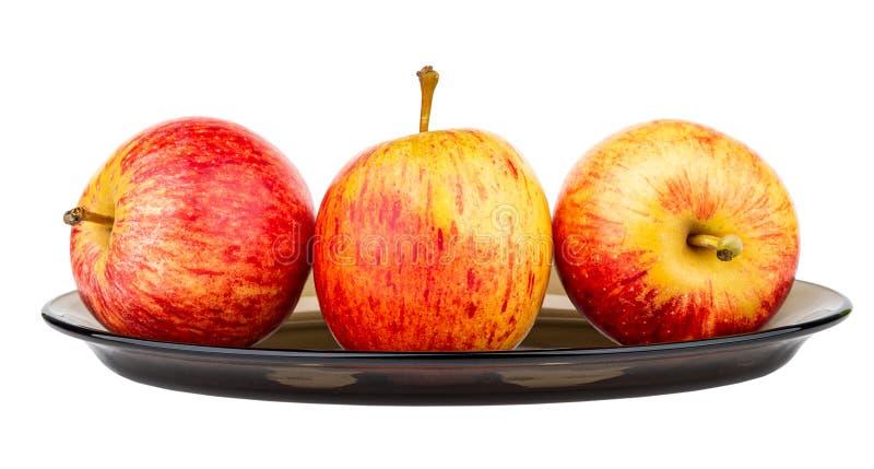 Tres manzanas rayadas en el plato marrón aislado en blanco imagenes de archivo
