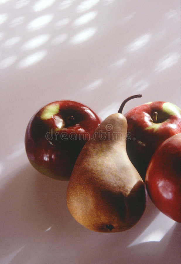 Tres manzanas y una pera imagen de archivo libre de regalías