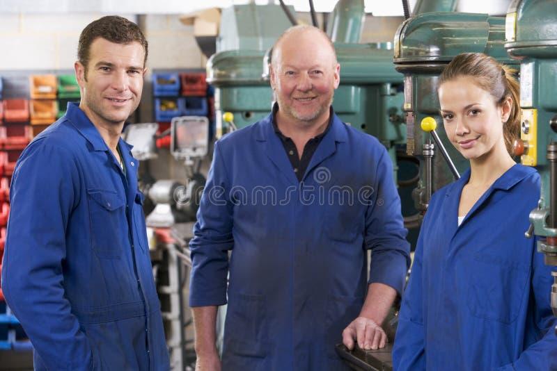 Tres maquinistas en espacio de trabajo hablando de la máquina fotos de archivo