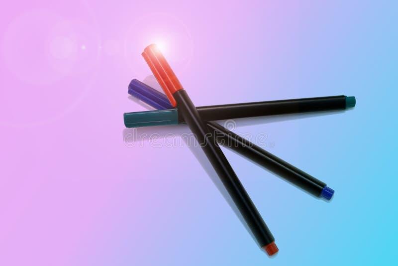 Tres marcadores del rotulador en azul en colores pastel un fondo rosado fotos de archivo