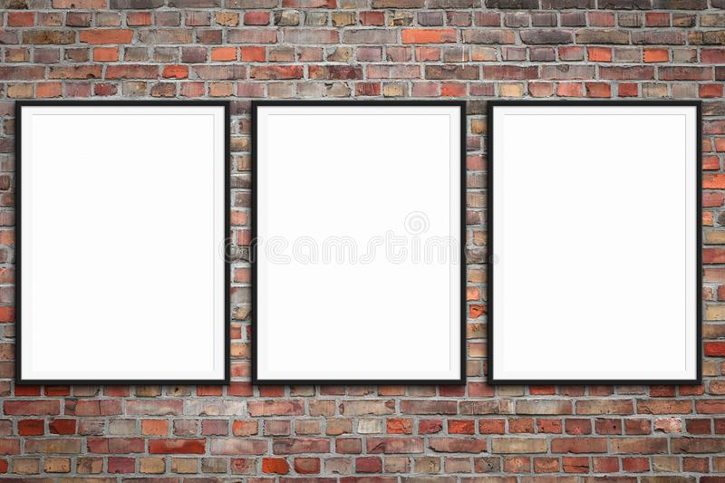 Tres marcos en blanco en la pared de ladrillo - maqueta enmarcada del cartel con el fondo de la pared de piedra imágenes de archivo libres de regalías