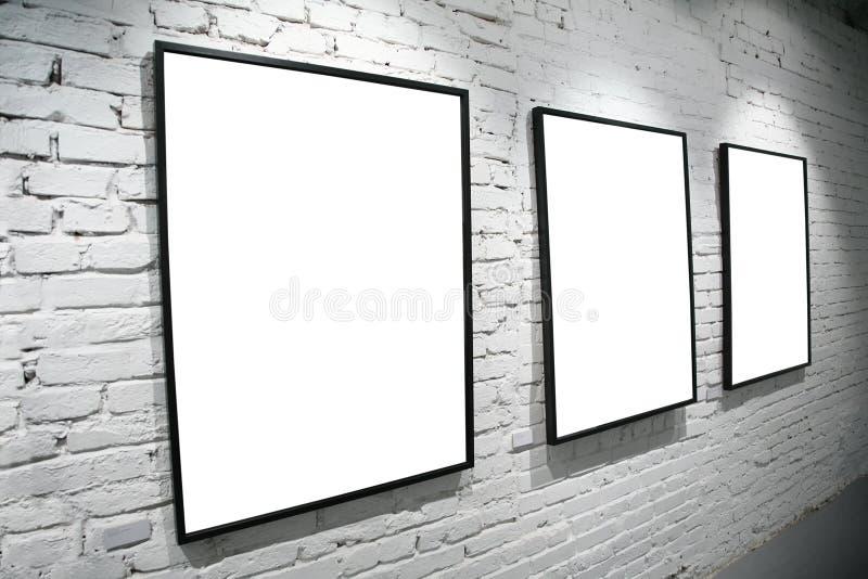 Tres marcos en la pared del blanco del ladrillo imagen de archivo