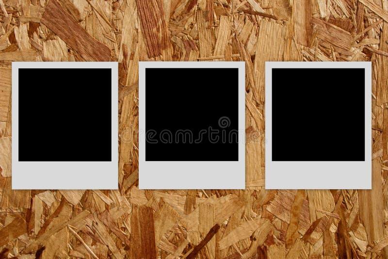 Tres marcos vacíos de la foto en el fondo de madera imagenes de archivo