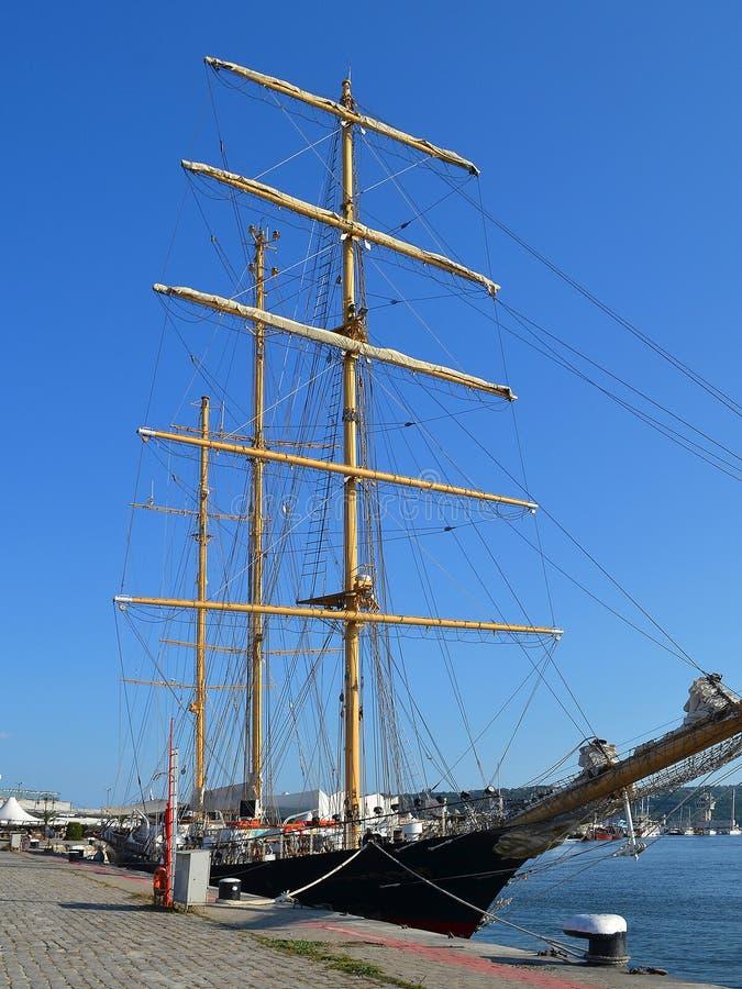 Tres masted el goleta con doblado encima de las velas amarradas en el embarcadero en el puerto en un día de verano imágenes de archivo libres de regalías