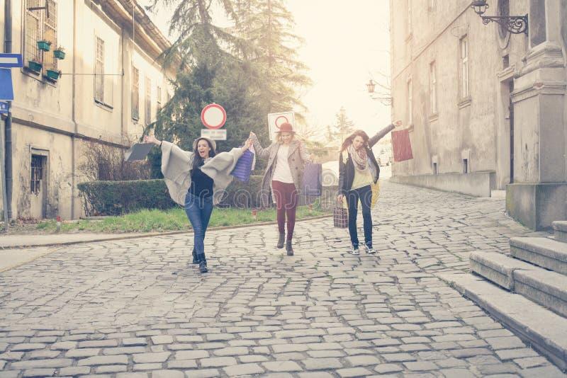 Tres mejores amigos que corren en la calle imagen de archivo