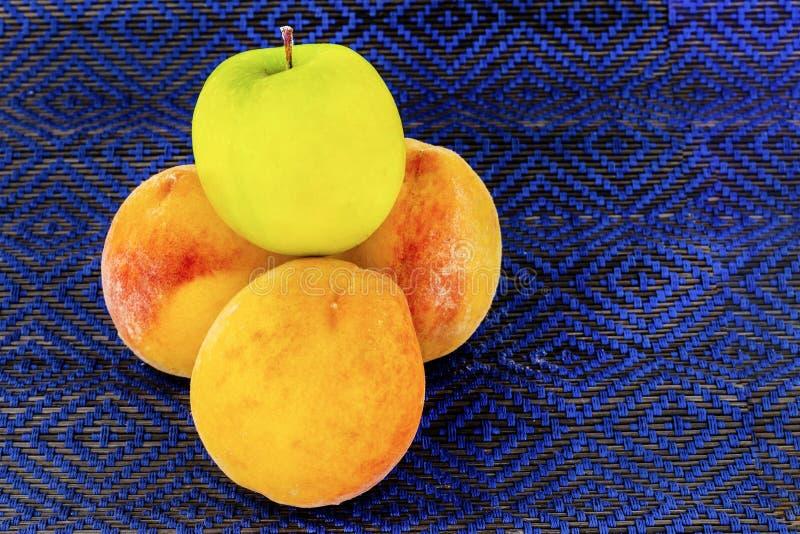 Tres melocotones jugosos maduros encima de un primer verde entero del sistema de la fruta de la manzana en un fondo oscuro foto de archivo libre de regalías