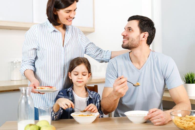 Tres miembros de la familia desayunan sano delicioso en la cocina, comen los copos de maíz con leche, disfrutan de unidad y imágenes de archivo libres de regalías