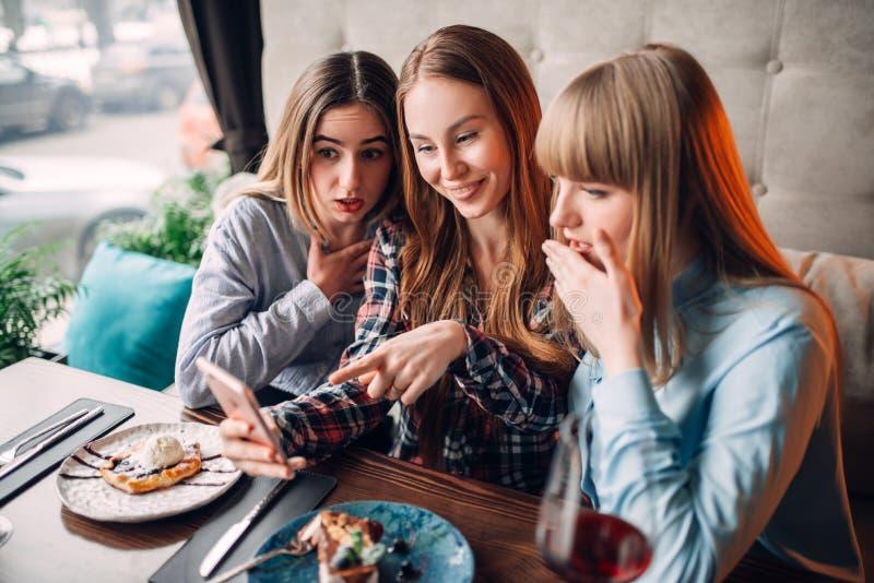 Tres miradas de los polluelos en las fotos en el teléfono en café fotos de archivo libres de regalías