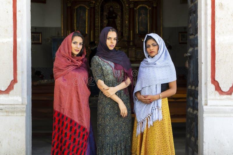 Tres modelos morenos hispánicos preciosos presentan en una iglesia católica foto de archivo libre de regalías