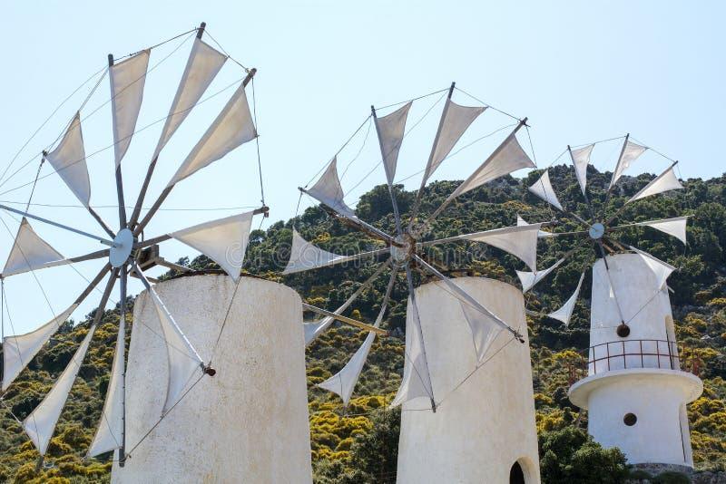 Tres molinoes de viento blancos viejos en Grecia imagenes de archivo