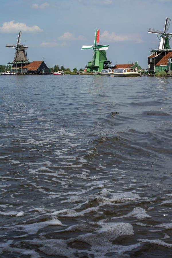 Tres molinos históricos en el agua azul en el día imagenes de archivo