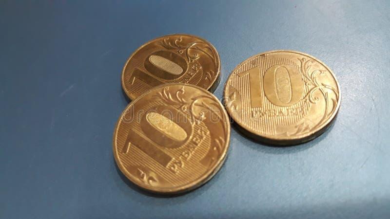 Tres monedas del metal mienten en la tabla fotografía de archivo