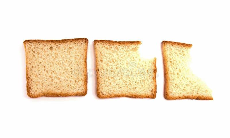 Tres mordeduras de pan de la tostada en el fondo blanco fotos de archivo