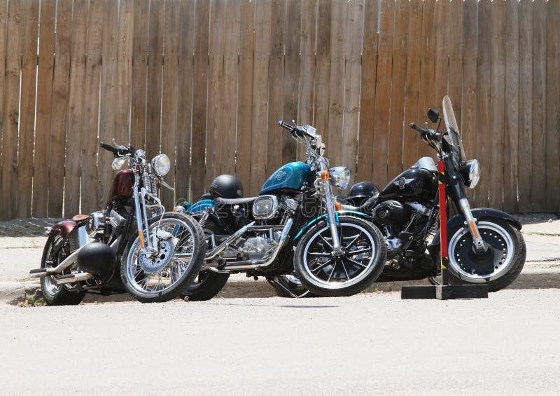 Tres motocicletas parqueadas por la cerca de madera fotos de archivo libres de regalías