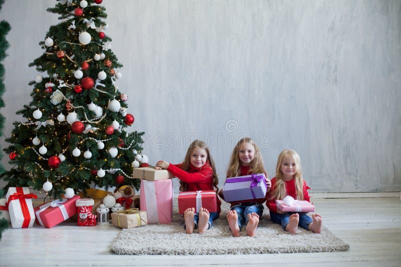Tres muchachas abren la guirnalda del árbol de navidad del Año Nuevo de los regalos de Navidad imagen de archivo libre de regalías