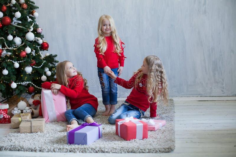 Tres muchachas abren la guirnalda del árbol de navidad del Año Nuevo de los regalos de Navidad imagenes de archivo