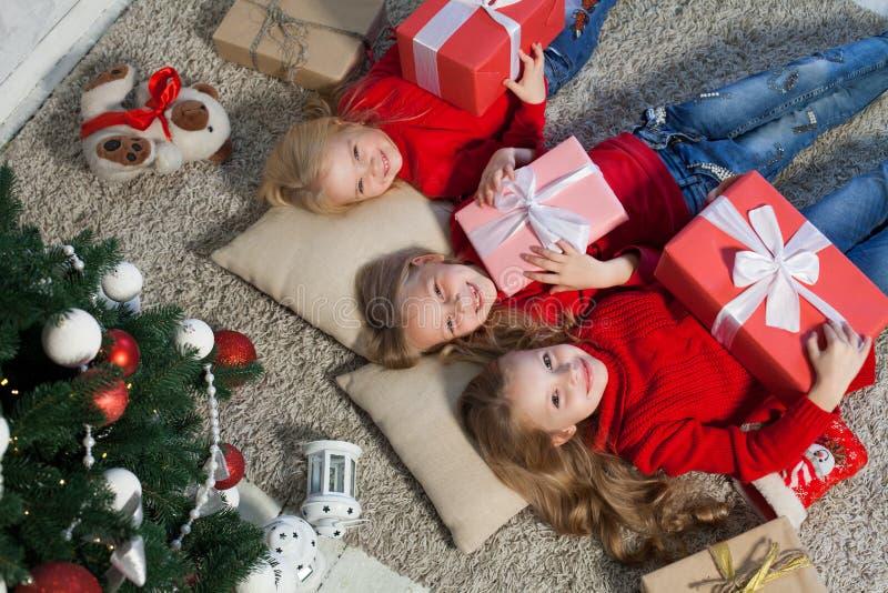 Tres muchachas abren luces de la guirnalda del árbol de navidad del Año Nuevo de los regalos de Navidad imagen de archivo