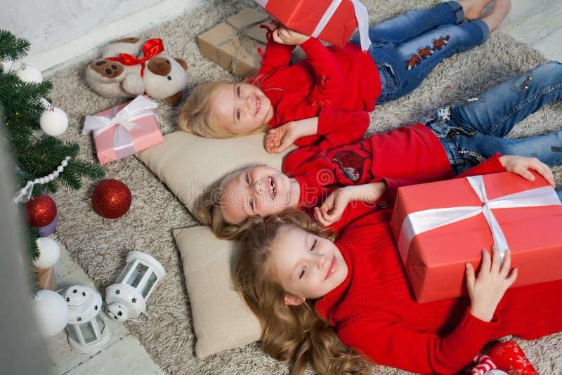 Tres muchachas abren luces de la guirnalda del árbol de navidad del Año Nuevo de los regalos de Navidad foto de archivo