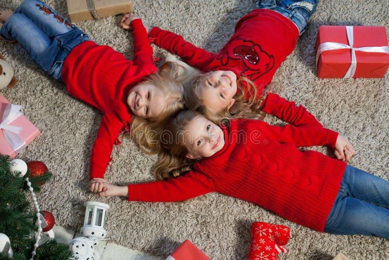 Tres muchachas abren luces de la guirnalda del árbol de navidad del Año Nuevo de los regalos de Navidad fotografía de archivo libre de regalías